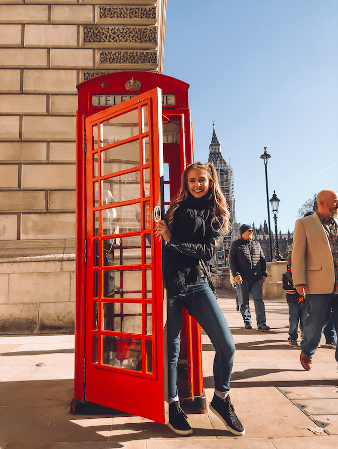cute girl at telephone book in london smiling wearing leather jacket and jeans