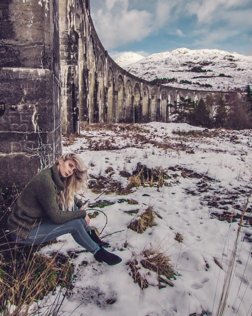 girl dressed like a badass slytherin by the glenfinnan viaduct in scotland