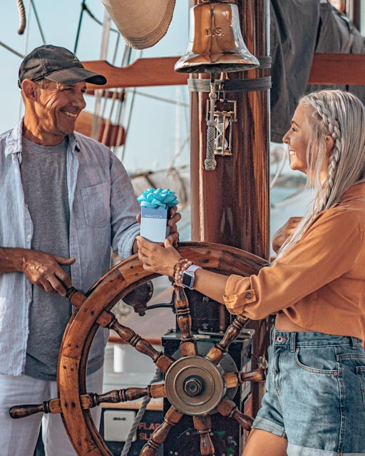 dad and daughter standing at helm of tall ship exchanging Fathers Day GIft by Nautica