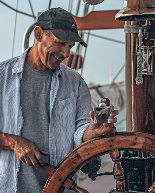 captain holding nautica voyage cologne at the helm of a tall ship