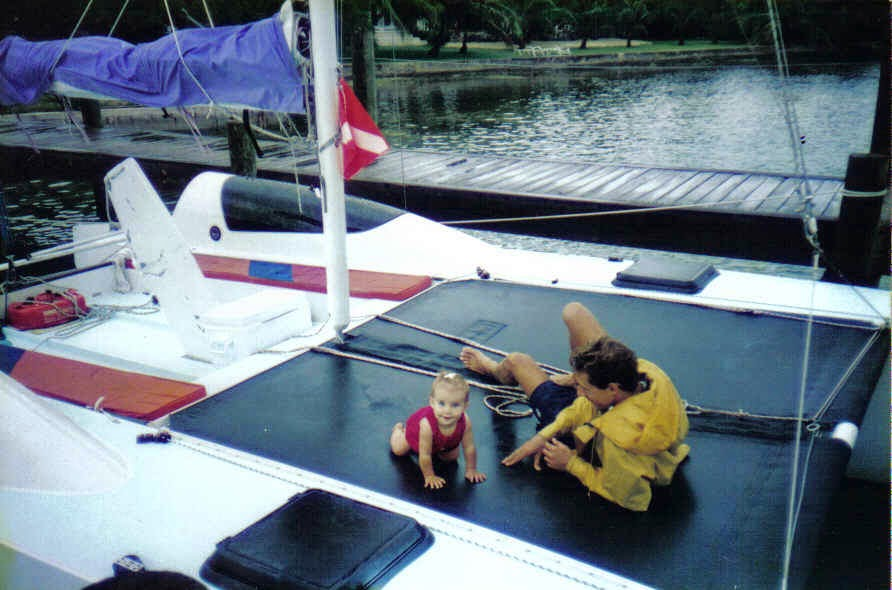 dad and baby playing on a sailing hobie catamaran