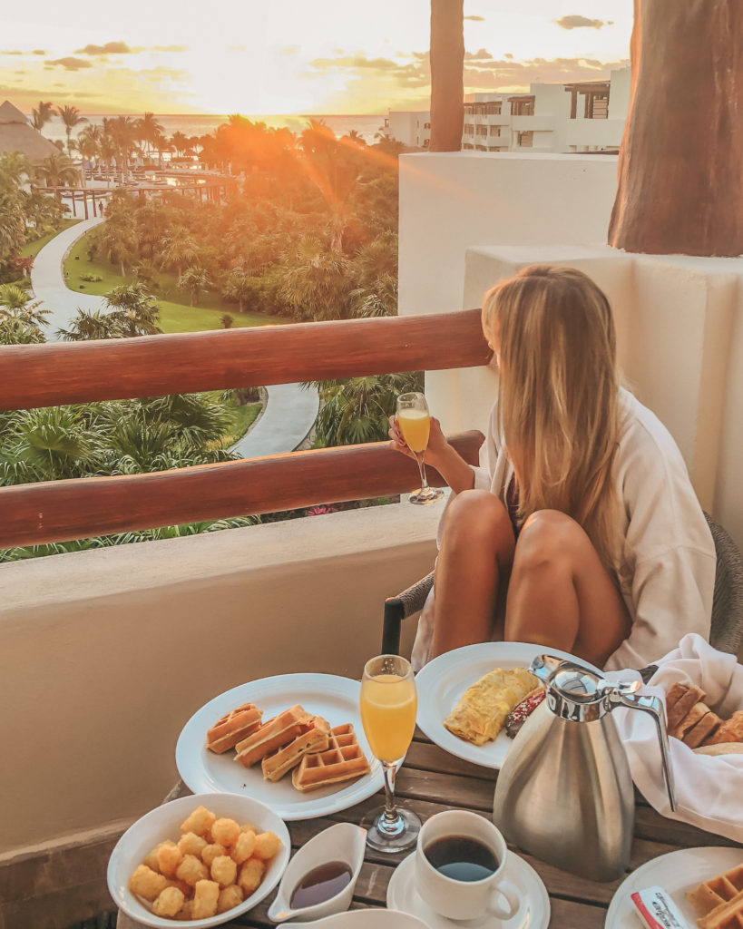 travel planner watching the sunrise with a full breakfast